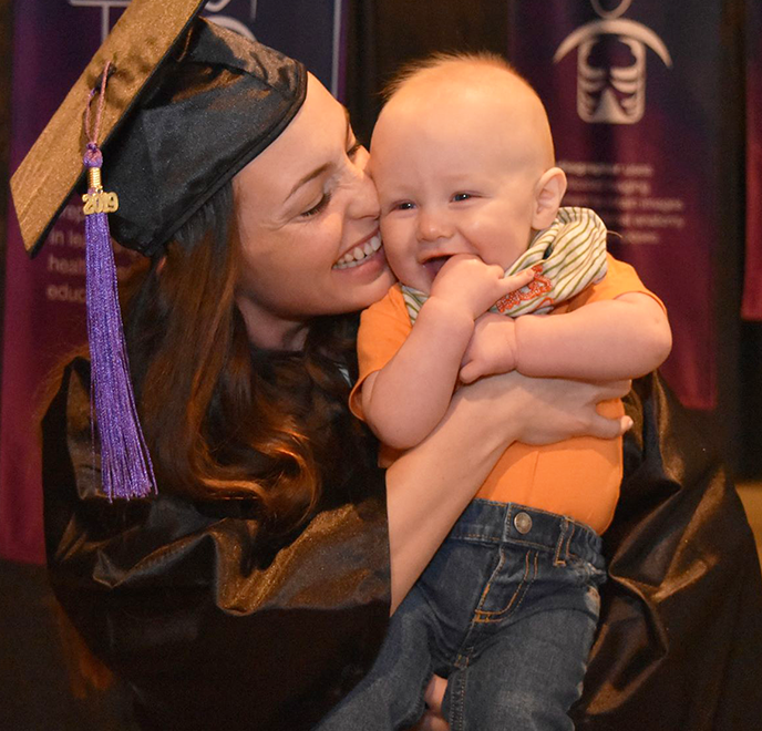 Graduate woman smiling with her baby